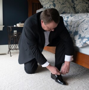 James tying his shoe for a wedding after getting relief from severe lower back pain